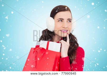 Brunette with ear muffs holding shopping bag full of gifts against blue vignette