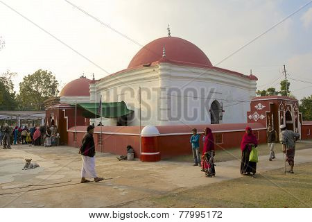 Unidentified pilgrims stand outside Ulugh Khan Jahan's mausoleum, Bagerhat, Bangladesh.