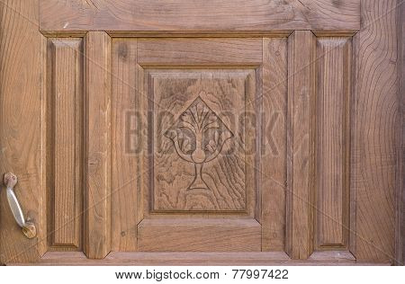 Old brown run-down religious decorated wooden door