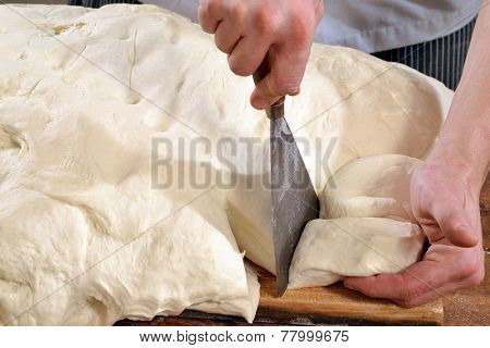 Cook preparing and cutting bread flour for pizza and bread