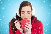 foto of muffs  - Woman in winter clothes enjoying a hot drink eyes closed against blue vignette - JPG