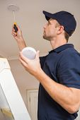 stock photo of smoke detector  - Handyman installing smoke detector with screwdriver on the ceiling - JPG