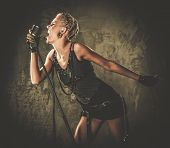 stock photo of singer  - Attractive steampunk singer with microphone  - JPG