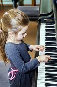 foto of grand piano  - Cute little girl playing grand piano in music school - JPG