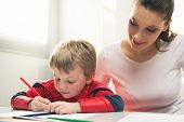 image of superhero  - Mother and superhero child playing and drawing together in the living room.
