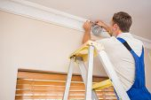 foto of scotch  - Handyman putting scotch on the ceiling in a new house - JPG