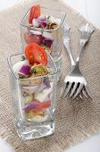 foto of plum tomato  - mediterranean salad as appetizer with mussel mozzarella plum tomato and purple onion in a shot glass
