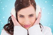 foto of muffs  - Pretty brunette with ear muffs against blue vignette - JPG