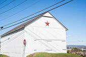 picture of mennonite  - Mennonite red star on end of white farm shed - JPG