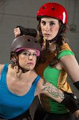 foto of roller-derby  - Two beautiful tough roller derby skaters with helmets - JPG