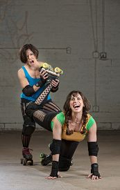 picture of roller-derby  - Bully roller derby skater twisting the leg of a woman - JPG