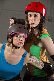 pic of roller-derby  - Two beautiful tough roller derby skaters with helmets - JPG
