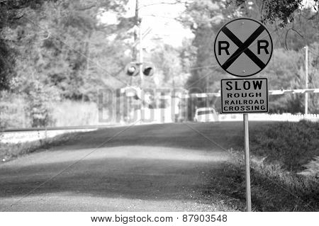 Slow Rough Railroad Crossing Sign In Black And White