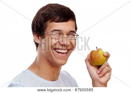 Close up portrait of young laughing hispanic man in glasses holding fresh apple isolated on white background