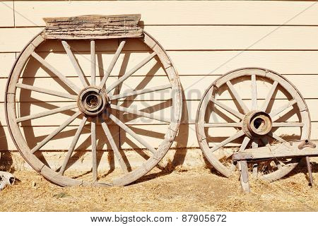 Two old faded wooden wheels leaning up against wooden wall under bright summer sunlight