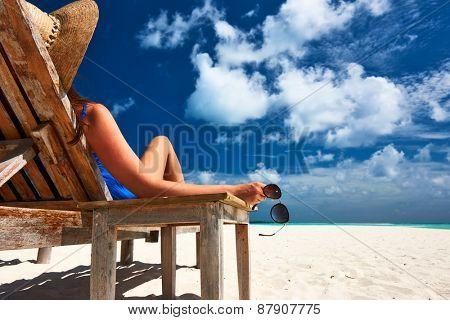 Woman at beautiful beach holding sunglasses