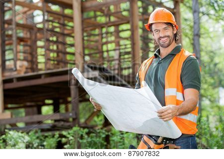 Portrait of happy male architect holding blueprint against incomplete timber cabin at construction site