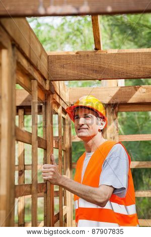 Smiling male construction worker standing in incomplete wooden cabin at site