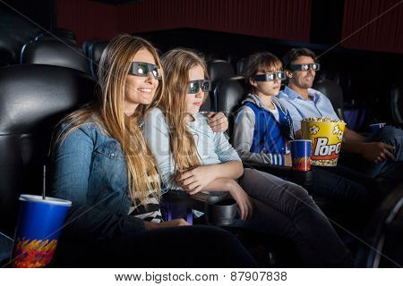Family of four with snacks watching 3D movie in cinema theater