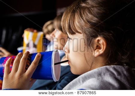 Closeup of girl drinking cola while watching movie with family in cinema theater