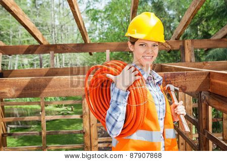 Portrait of happy female construction worker holding pipe and hammer in timber cabin at site