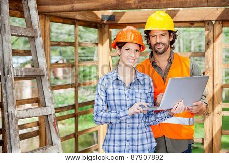 Portrait of confident male and female architects with laptop at construction site