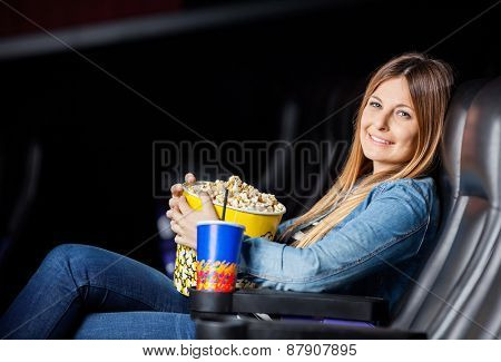 Side view portrait of smiling woman with snacks sitting at movie theater