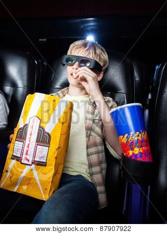 Boy eating popcorn while watching 3D movie in cinema theater
