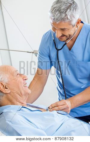 Smiling male caretaker examining senior man with stethoscope in bedroom at nursing home