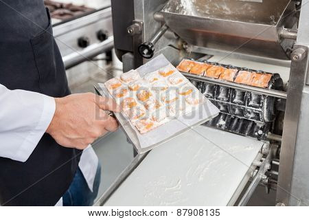 Midsection of male chef processing ravioli pasta in automated machine at commercial kitchen