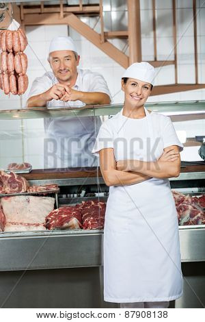 Portrait of male and female butchers at display cabinet in butchery