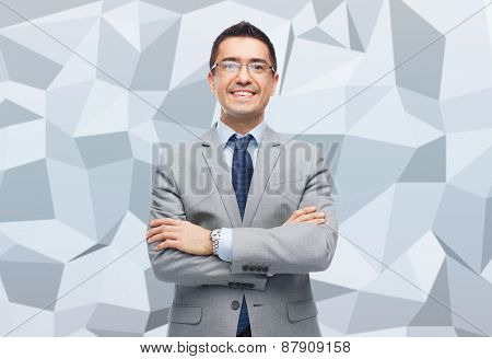 business, people, vision and office concept - happy smiling businessman in eyeglasses and suit over gray graphic low poly background