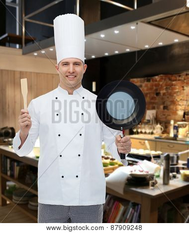 cooking, profession and people concept - happy male chef cook holding frying pan and spatula over restaurant kitchen