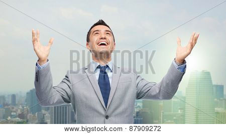business, people and success concept - happy businessman in suit with raised hands laughing and looking up over city background