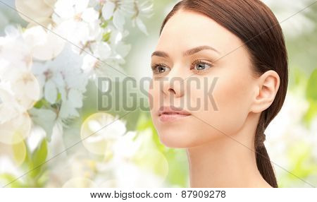 health, people, eco and beauty concept - beautiful young woman face over green blooming garden background