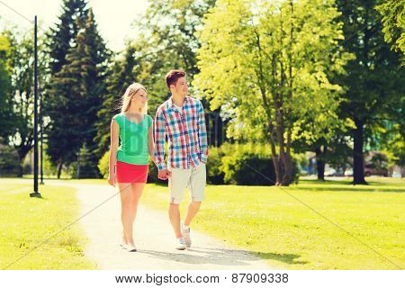holidays, vacation, love and friendship concept - smiling couple walking and holding hands in park