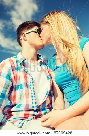 holidays, vacation, love and friendship concept - smiling couple kissing outdoors