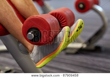 sport, fitness, bodybuilding, lifestyle and people concept - close up of man legs exercising on gym machine