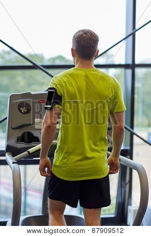 sport, fitness, lifestyle, technology and people concept - man with smartphone and earphones exercising on treadmill in gym from back