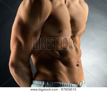 sport, bodybuilding, strength and people concept - close up of young man standing over black background