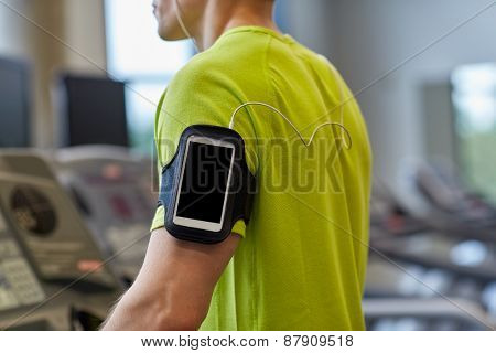 sport, fitness, lifestyle, technology and people concept - close up of man with smartphone and earphones exercising on treadmill in gym