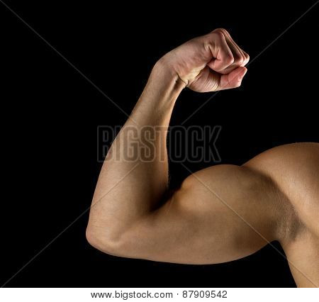 sport, bodybuilding, strength and people concept - close up of young man showing biceps over black background