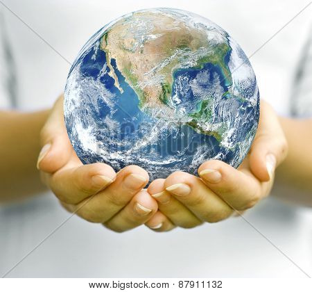 The open hands of woman and earth in. Elements of this image furnished by NASA