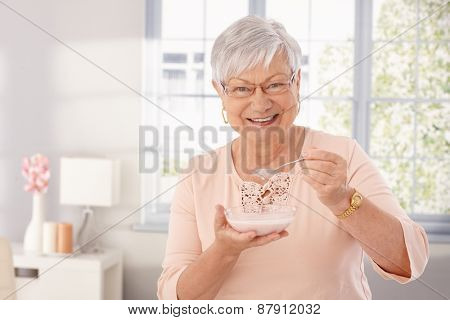 Happy old woman eating breakfast cereal, smiling, looking at camera.