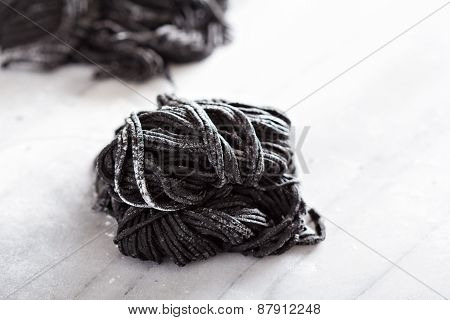 Squid ink homemade pasta on marble