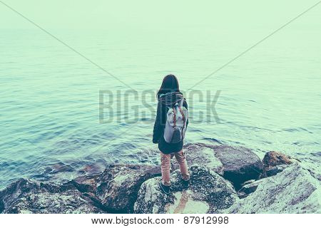 Woman Standing On Stone On Coastline