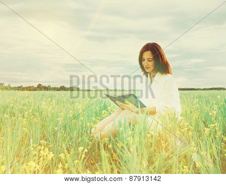 Girl reading a book on summer field