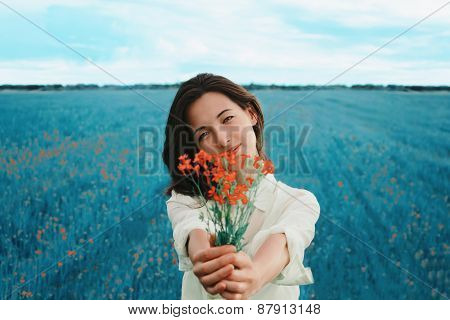 Beautiful Woman With A Bouquet Of Red Flowers