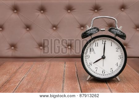 Vintage background with retro alarm clock on table upholstery leather pattern background
