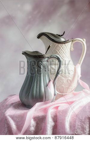 Two antique Victorian jugs on a table with pink ribbon and cloth